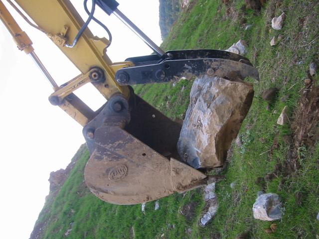 Hydraulic Excavator Thumb HT1850 grasping a large stone
