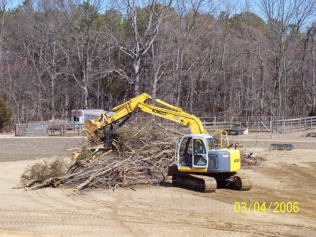KOBELCO with hydraulic thumb clearing brush