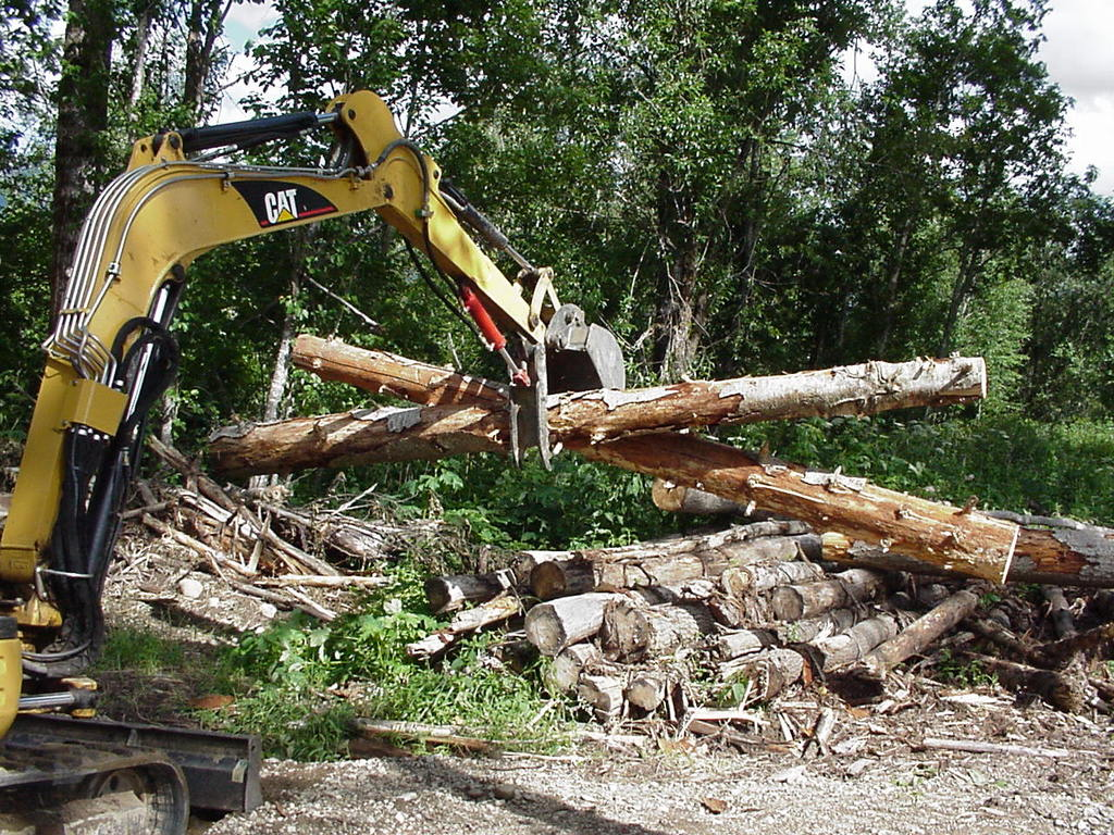 HT830 mini hydraulic thumb, installed on a CAT excavator, picking up two logs.