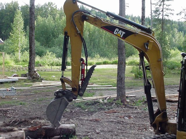 HT830 mini excavator thumb installed on a CAT mini excavator, with thumb in folded position