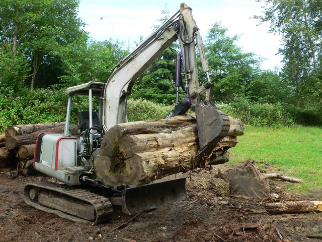 Ht830 hydraulic mini excavator thumb shown lifting a tree log