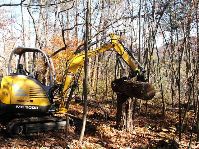 another action shot of the mustang me3003 picking up a log with the HT830 hydraulic mini excavator thumb by USA Attachments