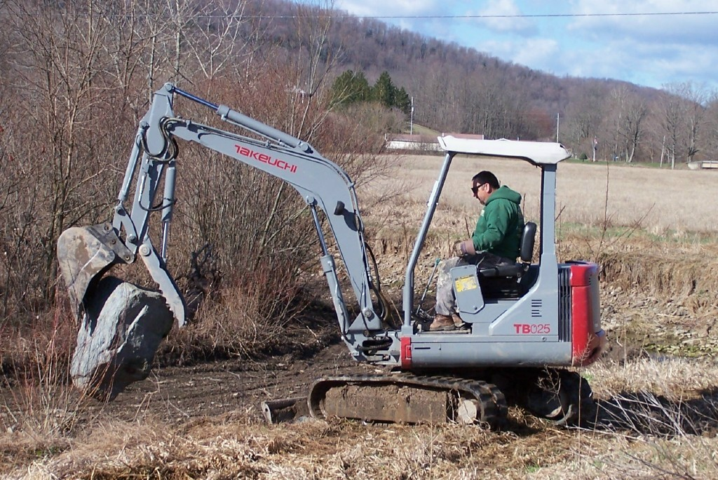 takeuchi tb025 mini excavator with thumb picks up a big rock