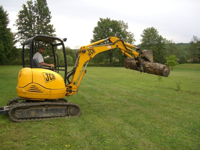 USA Attachments presents the HT830 mini excavator hydraulic thumb on a JCB mini excavator picking up a log.