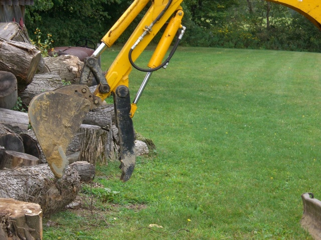 Mini excavator hydraulic thumb picking up logs