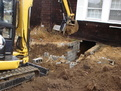 An HT830 mini hydraulic thumb clears out a foundation