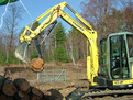 Another view of the YANMAR mini excavator with mini hydraulic thumb picking up a log