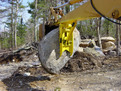 MT1230 excavator thumb, installed on an excavator, lifting a heavy stone.