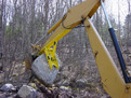 The MT1230 excavator thumb, installed on an excavator, lifts a very heavy stone.