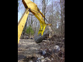 The MT1230 thumb, installed on an excavator, lifts a large stone.