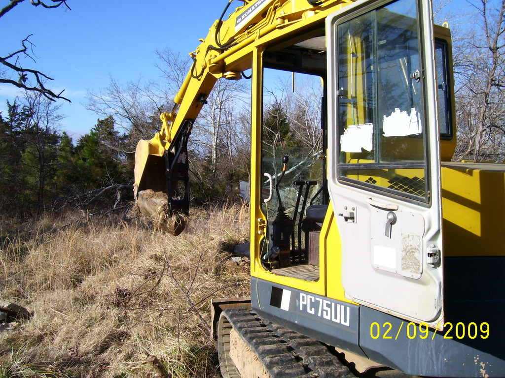 Komatsu PC75UU picking up a large stone with MT140 excavator thumb by USA Attachments