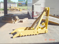 Yellow MT1240 excavator backhoe thumb waiting to be installed on a machine.
