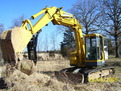 MT1240 excavator thumb installed on a Komatsu PC75UU picking up a large stone