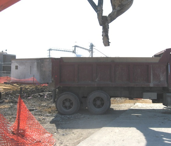 Mt3070 excavator thumb loading material into a dump truck