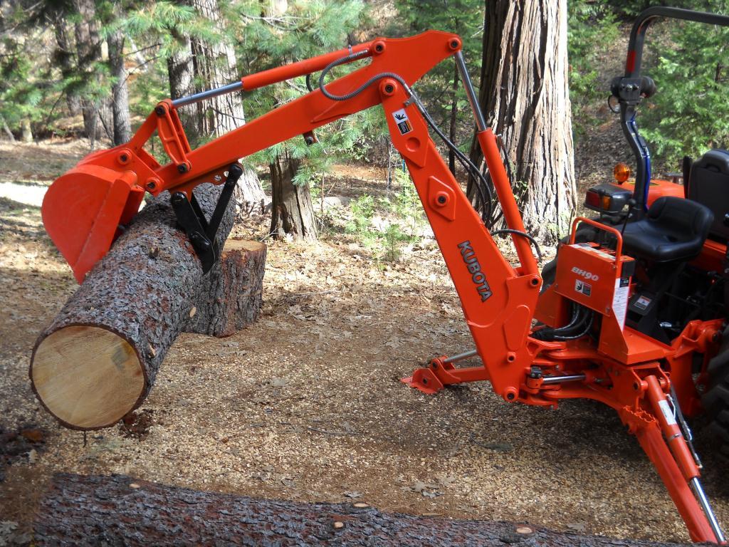 MT618 mini excavator thumb on a Kubota BH90 backhoe log lifting 1