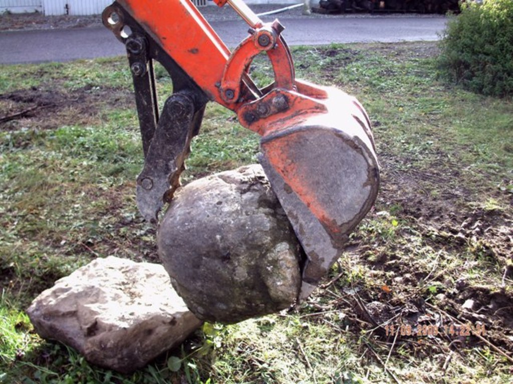 KUBOTA KH-41 with USA Attachments mini thumb installed grasping a large stone