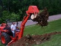 "kubota bh90 backhoe lifts a stump out of the ground with MT618, 6""x18"" mini thumb from USA Attachments"