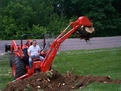 kubota bh90 backhoe lifts stump from ground with MT618 mini thumb