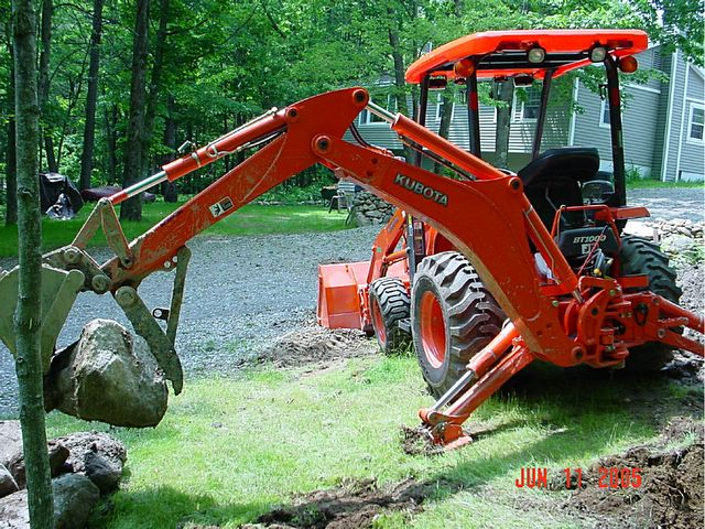 Another view of the MT824 thumb installed on the Kubota L39 mini backhoe moving stones.