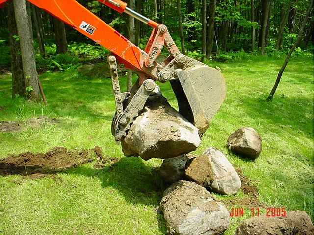 MT824 mini thumb moving stones installed on a KUBOTA L39 mini backhoe.