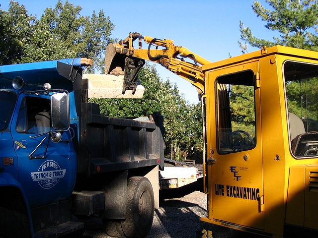 Deere 25 mini excavator loading concrete into a dump truck with 8