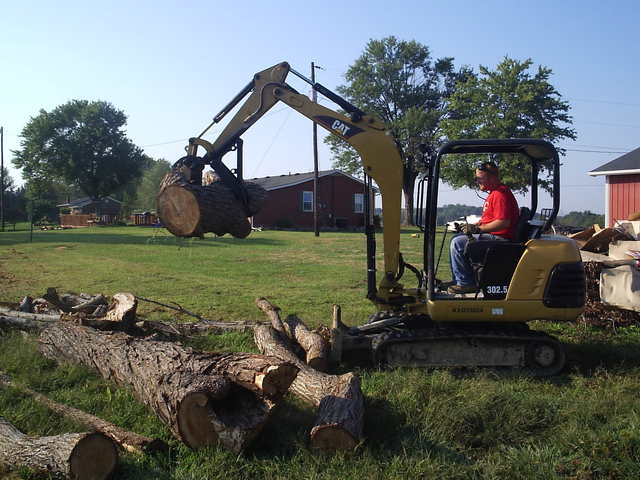 CAT 302.5 excavator picking up logs with MT824 mini excavator thumb by USA Attachments