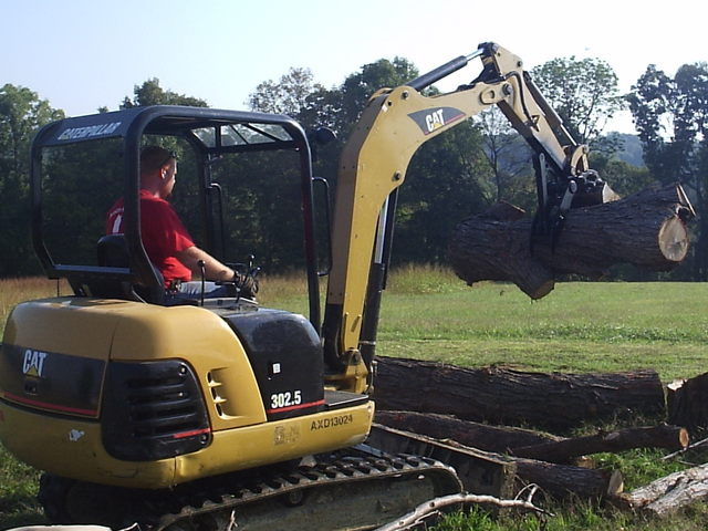 CAT 302.5 mini excavator with MT824 mini excavator thumb picking up logs