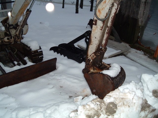MT824 mini excavator thumb installed on an excavator in the snow