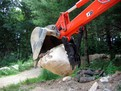 MT824 mini excavator thumb picking up stone, installed on a Kubota excavator