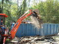 KUBOTA L35 tractor backhoe cleaning debris with a thumb from USA Attachments