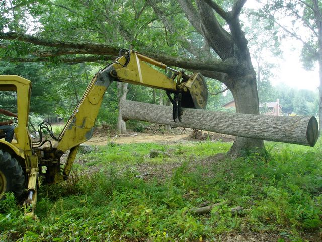 A log is being picked up by this MT830 mini excavator thumb.