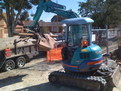 "Kubota mini excavator with 8""x30"" excavator thumb picks up scrap"