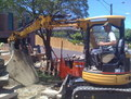 "CAT 303 SR mini excavator picks up a large slab of concrete with 8""x30"" thumb"