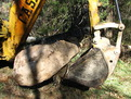 CASE backhoe with MT830 thumb moves stone